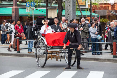 asakusa: TOKYO, JAPAN - CIRCA APR, 2013: Happy Japanese couple rides on the rickshaw in the Asakusa district. Asakusa district with ancient Sensoji shrine is famous place for people visiting Editorial