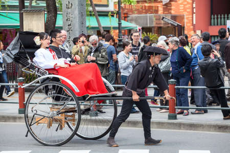 TOKYO, JAPAN - CIRCA APR, 2013: Man rides Japanese couple on the road at rickshaw in the Asakusa district. Asakusa district with old Sensoji shrine is famous place for people visiting