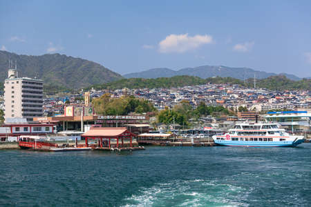 disembarking: MIYAJIMAGUCHI, JAPAN - CIRCA APR, 2013: Ferry piers of Matsudai Kisen and JR transportation company are in Miyajimaguchi port. View from the departing vessel. Two ferry-boats for Itsukushima island travel. The Hiroshima gulf, Japan.