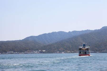 disembarking: MIYAJIMAGUCHI, JAPAN - CIRCA APR, 2013: Ferry-boat of JR company is in the Hiroshima gulf. Route to the island of Miyajima (Itsukushima). View from the city Miyajimaguchi.