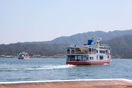 bateau: Miyajimaguchi, JAPON - CIRCA APR 2013: Ferry-boat de la société JR commence croisière à l'île de Miyajima (Itsukushima) à Hiroshima golfe. Vue de la jetée de la ville Miyajimaguchi