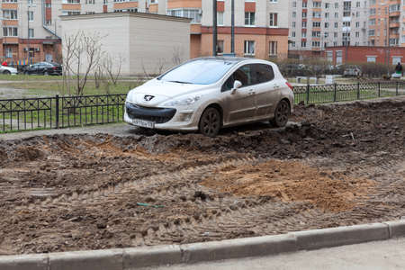 appartment: ST. PETERSBURG, RUSSIA - CIRCA APR, 2015: Vehicle is wrong parked and left on lawn while machinery makes urban land improvement. Russia appartment courtyard with parking lot Editorial