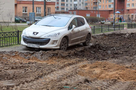 urban redevelopment: ST. PETERSBURG, RUSSIA - CIRCA APR, 2015: Car is wrong parked and left on lawn while machinery makes urban land improvement. Russia appartment courtyard with parking lot