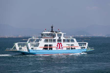 disembarking: MIYAJIMAGUCHI, JAPAN - CIRCA APR, 2013: The ferry of Matsudai Kisen company comes to Miyajimaguchi town pier. Two ferry-boats for Itsukushima island travel. The Hiroshima gulf, Japan. Editorial