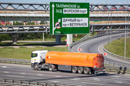 encircling: SAINT-PETERSBURG, RUSSIA - CIRCA JULY, 2014: Gasoline truck drives on the Saint-Petersburg city highway with a orange tank. The Saint-Petersburg city encircling highway