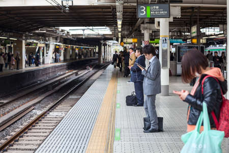 rail route: TOKYO, JAPAN - CIRCA APR, 2013: Passengers wait for train arrival on the Japanese rail station at Yamamoto line. The Yamamoto is a railway loop line in Tokyo, Japan Editorial