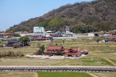 small country town: HIROSHIMA, JAPAN - CIRCA APRIL, 2013: Provincial area with traditional architecture is in Hiroshima prefecture, the view from the train window