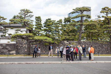 the elderly residence: TOKYO, JAPAN - CIRCA APR, 2013: Group of Asian tourists stands near the Tokyo Imperial Palace entrance and wait for tour beginning. The Tokyo Imperial Palace is the main residence of the Emperor of Japan