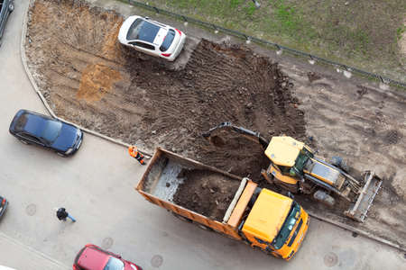 ST. PETERSBURG, RUSSIA - CIRCA APR, 2015: Wrong parking car is on lawn while construction machinery works for extension of parking area of apartment building. Creation of living environment in city