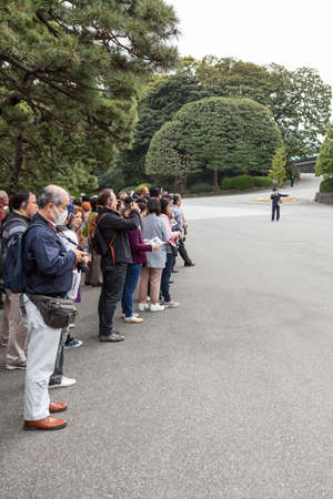 sightseers: TOKYO, JAPAN - CIRCA APR, 2013: Tourists listen the guide while visiting the inner yard of Tokyo Imperial Palace. Tokyo Imperial Palace is the main residence of the Emperor of Japan