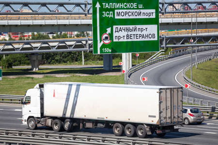 SAINT-PETERSBURG, RUSSIA - CIRCA JULY, 2014: Exit to the sea port from the Saint-Petersburg city encircling highway. Container cargo truck drives on road. The federal public ringroad