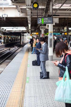 file d attente: TOKYO, JAPON - CIRCA APR 2013: Les gens attendent le train pour l'arrivée sur la station ferroviaire japonaise à la ligne Yamamoto. Le Yamamoto est une ligne de boucle ferroviaire à Tokyo, au Japon, Éditoriale