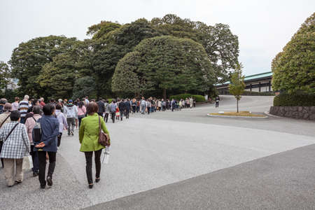 sightseers: TOKYO, JAPAN - CIRCA APR, 2013: Tourists with guides visit the inner yard of Tokyo Imperial Palace. Tour course with people are in line. Tokyo Imperial Palace is the main residence of the Emperor of Japan