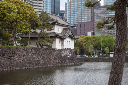moat wall: TOKYO, JAPAN - CIRCA APR, 2013: Edo Castle towers, wall and moat with high-rise modern buildings are in surroundings of the Tokyo Imperial Palace. The Tokyo Imperial Palace is the main residence of the Emperor of Japan Editorial