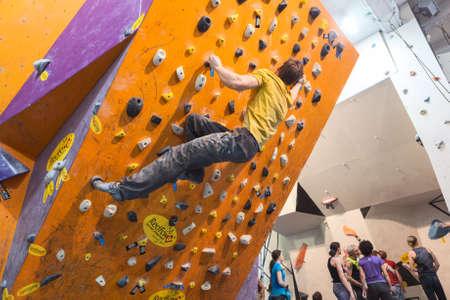 escalando: SAN PETERSBURGO, Rusia - alrededor de febrero de 2015: Campeonato de escalada es en IgelsClub. Deportistas trepan las paredes. Igelsclub es un parque parkour con la escalada gimnasio y trampolines Editorial