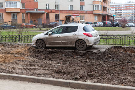 ST. PETERSBURG, RUSSIA - CIRCA APR, 2015: Wrong parking car is on middle of lawn while construction machinery works for extension of parking area of apartment building. Creation of living environment in city