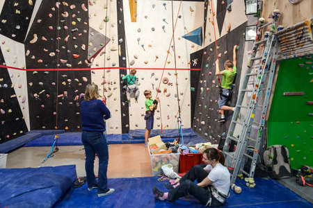 recreational climbing: SAINT-PETERSBURG, RUSSIA - CIRCA FEB, 2015: Gym with rock-climbing wall for beginners, adults and kids have workout with instructor. Igelsclub is a parkour park with climbing gym and trampolines Editorial