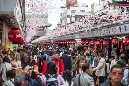 asakusa: TOKYO, JAPAN - CIRCA APRIL, 2012: Tourists walk on Nakamise Dori in Sensoji shrine. The Nakamise Dori is a street with food and souvenirs shops in Senso-ji shrine, Asakusa Editorial