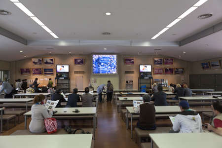 watch video: TOKYO, JAPAN - CIRCA APR, 2013: Group of tourists watch video in Someikan waiting room before a walking tour in the Tokyo Imperial Palace ground. The Tokyo Imperial Palace is the main residence of the Emperor of Japan