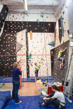 rockclimbing: SAINT-PETERSBURG, RUSSIA - CIRCA FEB, 2015: Gym with rock-climbing wall for beginners, people have workout with instructor. Igelsclub is a parkour park with climbing gym and trampolines