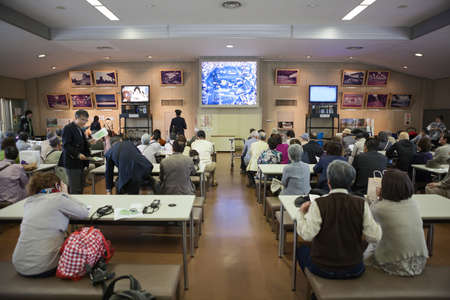 watch video: TOKYO, JAPAN - CIRCA APR, 2013: Tourists watch video in Someikan waiting room before a walking tour in the Tokyo Imperial Palace ground. The Tokyo Imperial Palace is the main residence of the Emperor of Japan
