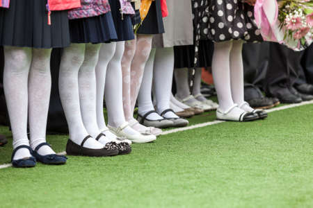 school uniforms: Legs in the boots of little girls standing in line