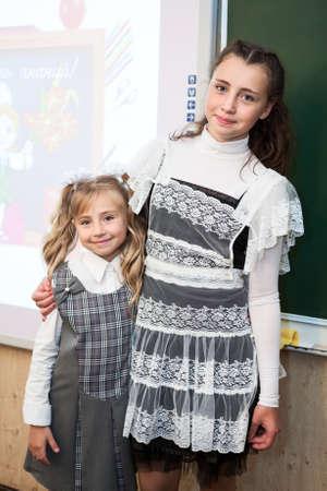 schoolgirl uniform: Two sisters of different ages, schoolgirls standing near school blackboard Stock Photo