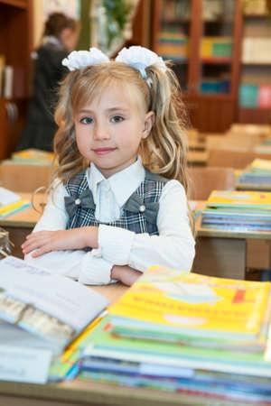 uniforme escolar: Primero-forma colegiala linda que se sienta en el escritorio de la escuela en el aula, mirando a la cámara