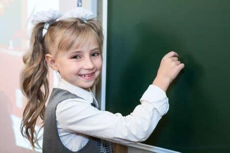 schoolgirl uniform: Happy schoolgirl standing near green blackboard with chalk in hand Stock Photo
