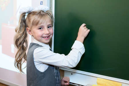 schooler: First grade pupil a girl writing on green blackboard at school lesson Stock Photo