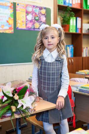 Cute schoolgirl in school uniform standing near desk in classroom