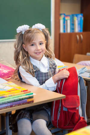 schooler: Schoolgirl in uniform sitting at desk and getting out things of bag Stock Photo