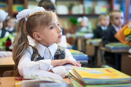 schoolgirl in uniform: Schoolgirl with folded hands sitting at school desk at lesson, copyspace
