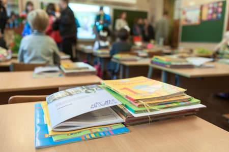 day book: ST. PETERSBURG, RUSSIA - CIRCA SEP, 2014: School exercise and ABC books are on the desk in classroom. Parents with kids are indoor. Children go back to school at first time in September