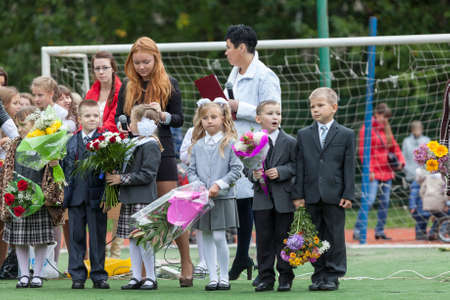 schoolyard: ST. PETERSBURG, RUSSIA - SEP, 1, 2014: First-grade pupils and teacher are in schoolyard. Children go back to school at first time in September