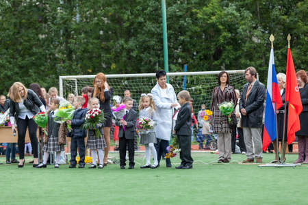 schoolyard: ST. PETERSBURG, RUSSIA - SEP, 1, 2014: First-grade students and teacher are in schoolyard. Children go back to school at first time in September