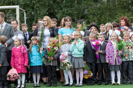 schoolyard: ST. PETERSBURG, RUSSIA - SEP, 1, 2014: School line is in schoolyard with first-grade pupils and teacher. Children go back to school at first time in September Editorial