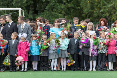 schoolgirl uniform: ST. PETERSBURG, RUSSIA - SEP, 1, 2014: First-grade pupils and teacher are in schoolyard. Children go back to school at first time in September