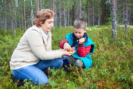 chicouté: Mère d'âge mûr et son fils manger la chicouté alors qu'il était assis dans la forêt marécageuse