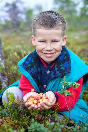 buisson: Préscolaire garçon tenant poignée de chicouté et en regardant la caméra Banque d'images