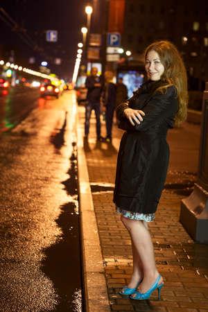 prostituta: Mujer congelada bonita en talones capa y altas negras caminando solo en la acera en la ciudad la noche