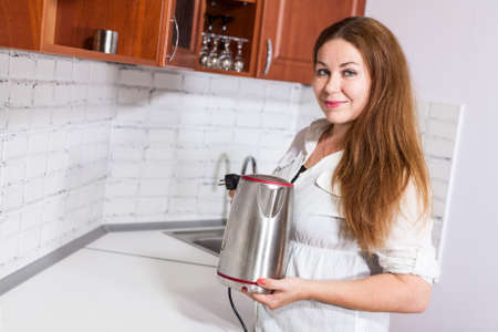 electric tea kettle: Woman with steel electric tea kettle in hands, copy space in front of Stock Photo