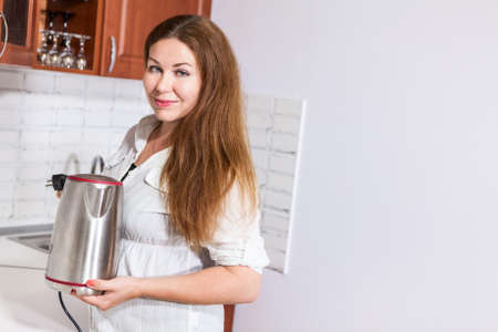 charlady: Caucasian woman with steel electric tea kettle in hands, copy space at back Stock Photo
