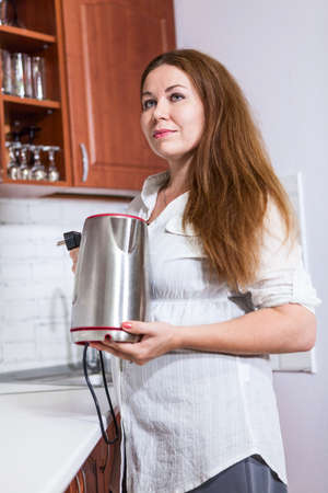 electric tea kettle: Thoughtful Caucasian woman with steel electric tea kettle in hands, domestic kitchen
