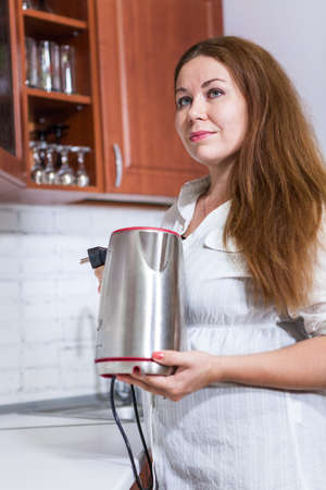 teakettle: Caucasian woman putting steel electric teakettle at the white countertop in kitchen Stock Photo