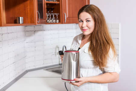 electric tea kettle: Housewife stands near white countertop with steel electric tea kettle in hands, copy space Stock Photo