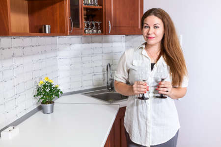 woman  glasses: Caucasian woman stands near counter with two wine glasses in hands, domestic kitchen
