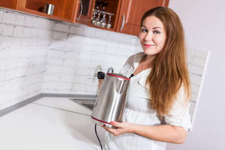 electric tea kettle: Housewife putting steel electric tea kettle at the white countertop in kitchen