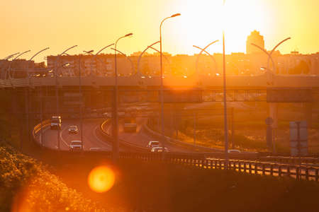 sunset city: Driving vehicles on city ring road at orange sunset at evening