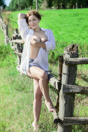 sexy girl nude: Sexy woman in a white shirt on naked body and jeans shorts covering her breast at the nature